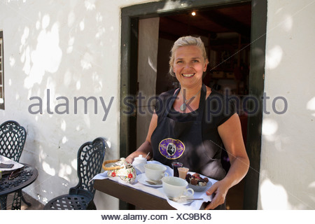 Woman serving tea and chocolate - Stock Photo