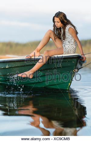 Sweden, Vastmanland, Hallefors, Bergslagen, Portrait of girl (10-11) sitting on boat - Stock Photo