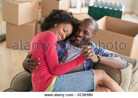 Mid adult couple on armchair in new home - Stock Photo