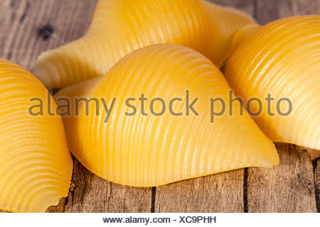 Conchiglie pasta, some seashells on wooden plank - Stock Photo