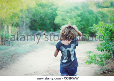 Rear View Of Woman Walking On Pathway - Stock Photo