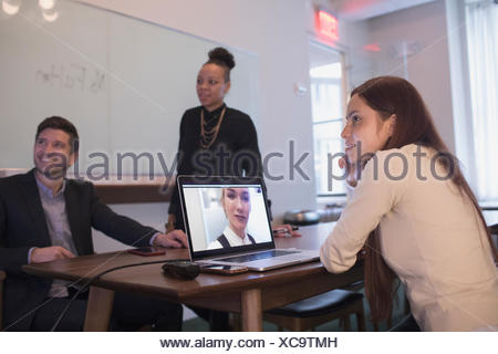 Young professionals in conference room working on laptop. - Stock Photo