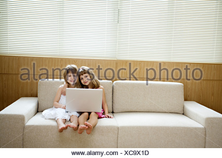 Two girls sitting in a sofa with a computer. - Stock Photo