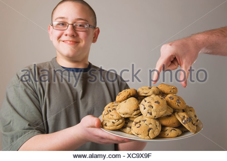 A Hand Taking A Cookie From A Plate Of Cookies Being Held By A Boy - Stock Photo