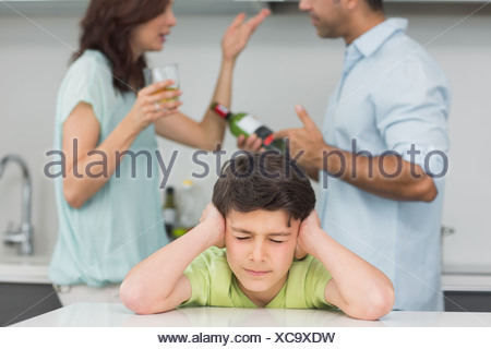 Sad young boy covering ears while parents quarreling - Stock Photo