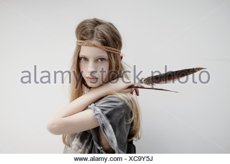 Portrait of girl wearing leather braid around head, holding feather - Stock Photo