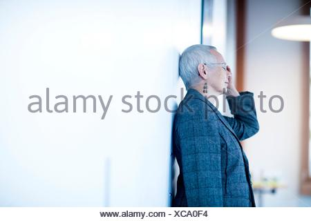 Side view of mature woman leaning against wall, hand on head, eyes closed looking stressed - Stock Photo
