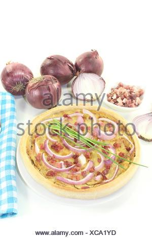 Zwiebelkuchen mit Lauch und Schinkenspeck vor hellem Hintergrund - Stock Photo