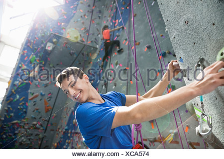 Two people climbing on climbing wall at gym - Stock Photo
