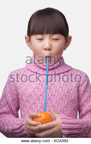Portrait of young girl drinking an orange with a straw, studio shot - Stock Photo