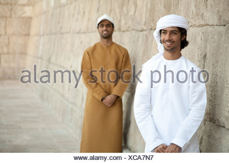 Middle Eastern men looking at by stone wall - Stock Photo