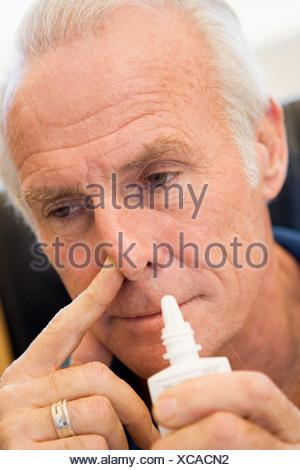 Senior Man Using Nasal Spray - Stock Photo