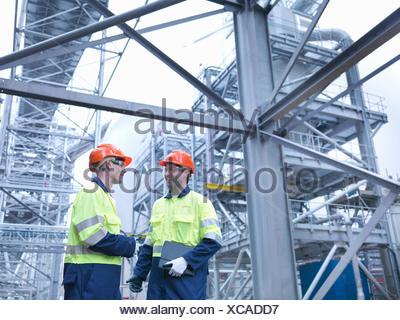 Workers in discussion in biomass facility - Stock Photo