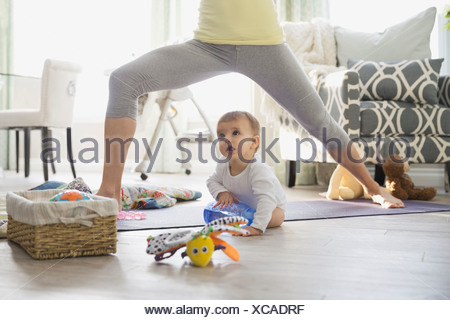 Mother practicing yoga by baby at home - Stock Photo