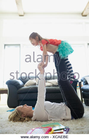 Mother lifting daughter with legs living room rug - Stock Photo