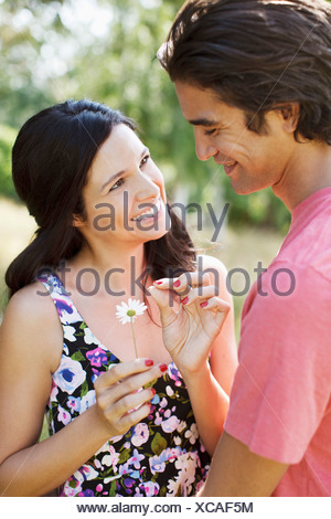 Smiling couple plucking petals from daisy - Stock Photo