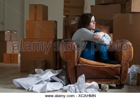 Teenage girl in armchair in new home - Stock Photo