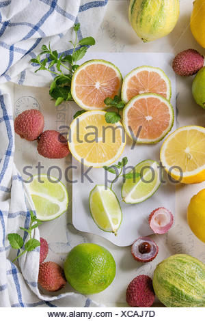Variety of whole and sliced citrus fruits pink tiger lemon, lemon, lime, mint and exotic lichee on white chopping board with kitchen towel over white  - Stock Photo