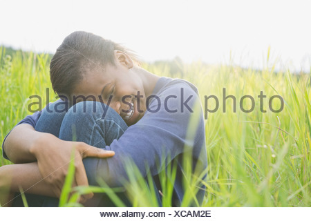 Happy teenage girl sitting outdoors in field - Stock Photo