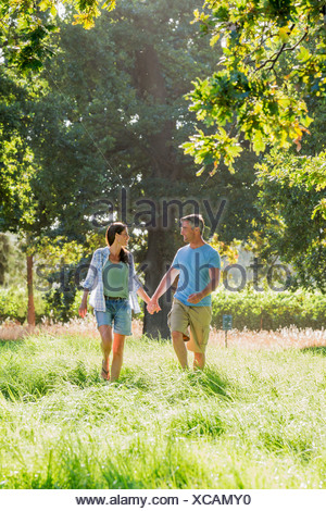 Romantic Couple Walking In Beautiful Countryside - Stock Photo
