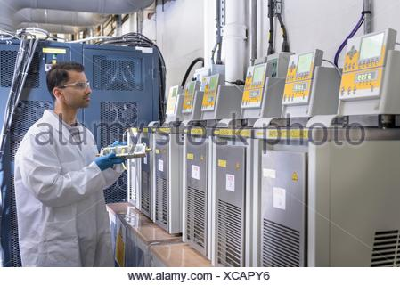 Scientist with lithium ion battery aging equipment in battery research facility - Stock Photo