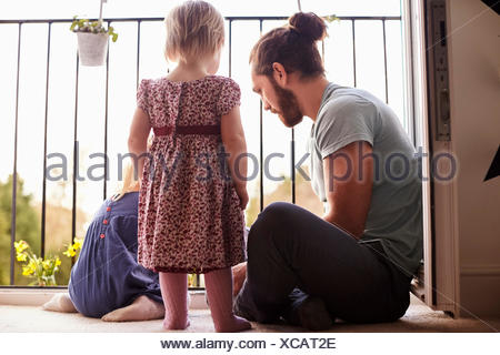 Father With Children At Home Watering Plants On Balcony - Stock Photo
