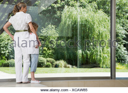 Woman and young girl standing in front of large window - Stock Photo