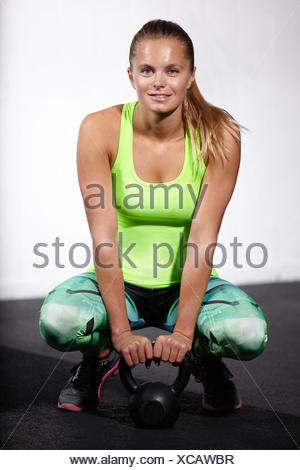 Portrait of young woman crouching with kettle bell in gym - Stock Photo