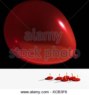 Balloon hovering over sharp pins - Stock Photo