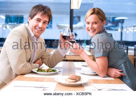 Couple proposing toast in restaurant, smiling, portrait - Stock Photo
