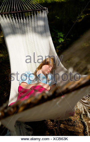 Sweden, Dalarna, Falun, Young woman lying on hammock in forest - Stock Photo