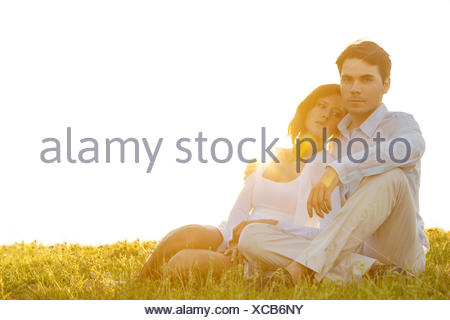 Portrait of confident young man sitting with girlfriend on grass against clear sky - Stock Photo