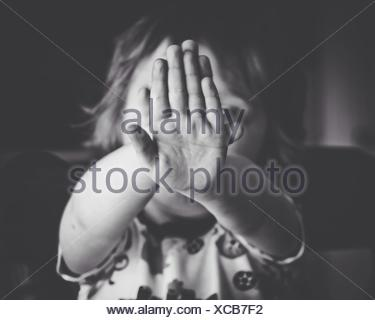Close-Up Portrait Of Girl Hiding Face - Stock Photo