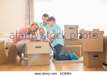 Family unpacking cardboard boxes at new home - Stock Photo