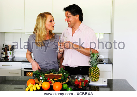Young couple clinking glasses, dessert and fruit in the foreground - Stock Photo