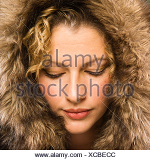 Caucasian young adult woman wearing fur hood with eyes closed - Stock Photo