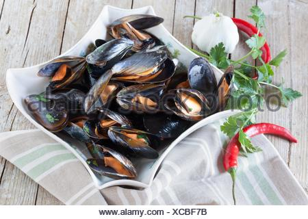 Plate with sauteed mussels decorated with fresh parsley, garlic and red chili pepper. - Stock Photo