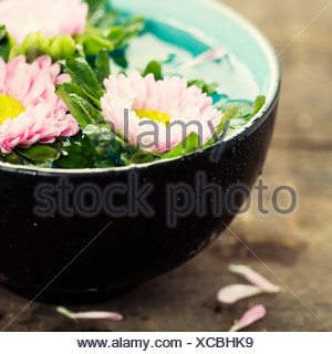 bowl of water and flowers in grunge style - Stock Photo