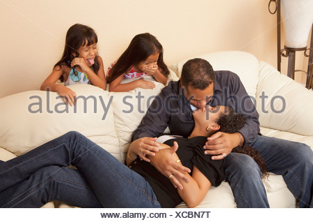 Girls Watching Their Parents Kissing - Stock Photo
