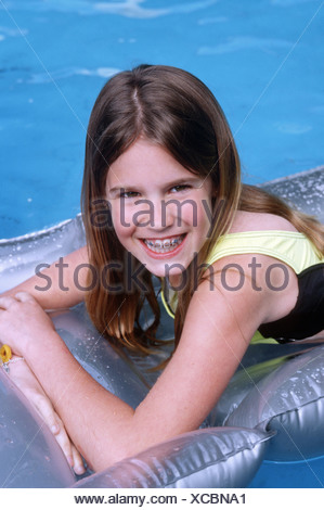 Caucasian female preteen floating on a raft in a swimming pool - Stock Photo