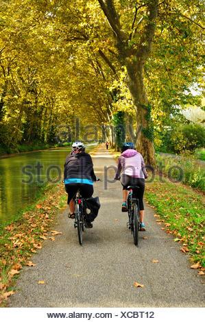 two cyclists on towpath beside the Canal de Garonne near Marmande, Lot-et-Garonne Department, Aquitaine, France - Stock Photo
