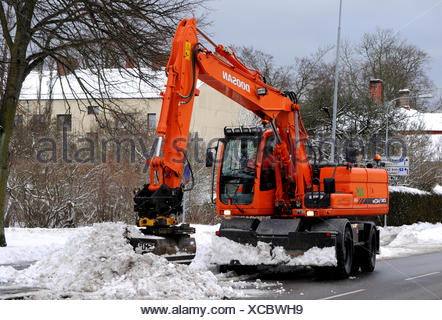 Snow-clearing with excavator in Sweden, Scandinavia, Europe - Stock Photo