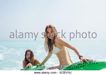 Portrait of two young female friends wearing bikinis playing on inflatable crocodile in sea - Stock Photo