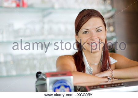 young barmaid behind the bar - Stock Photo