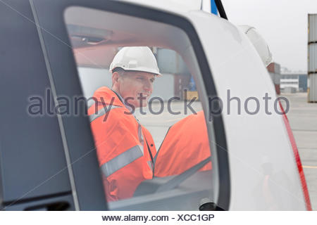 Engineers conversing beside car in shipping yard - Stock Photo