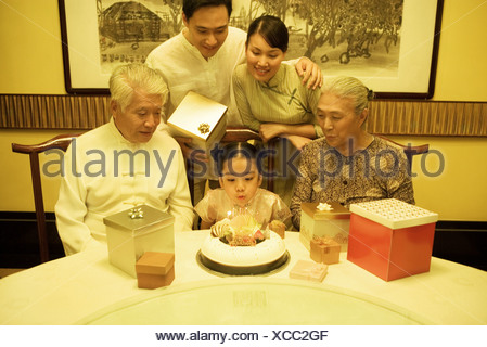 Three generation family having birthday party for girl, girl blowing out candles on cake - Stock Photo