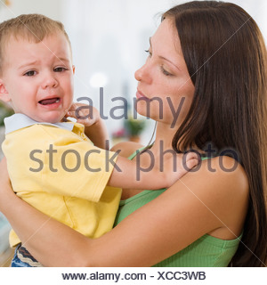 Mother holding crying baby - Stock Photo