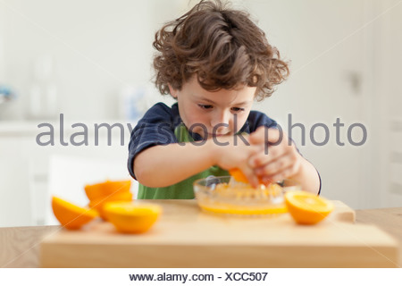 Boy squeezing oranges to make juice - Stock Photo