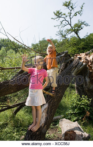 Brother and sister on a fallen tree - Stock Photo