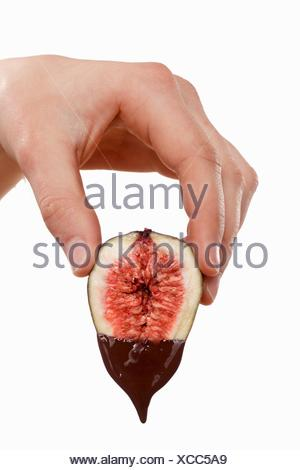 Hand holding a fig dripping with melted chocolate - Stock Photo